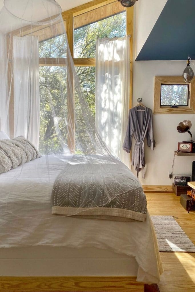 Bed in Acorn tiny home with large window view