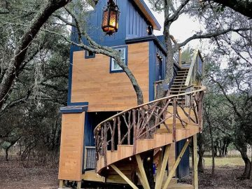 The Acorn tiny home with blue siding and spiral staircase