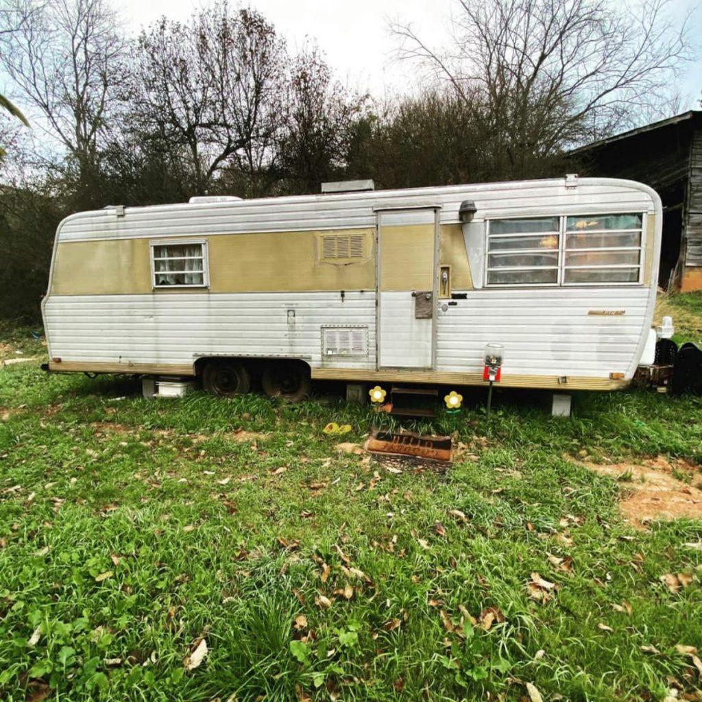 1971 Boles Aero camper in yard in poor condition