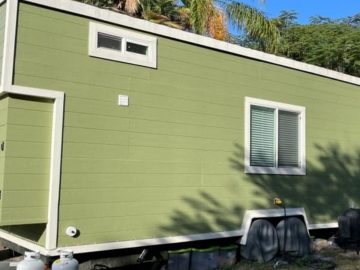 Green tiny house with white trim