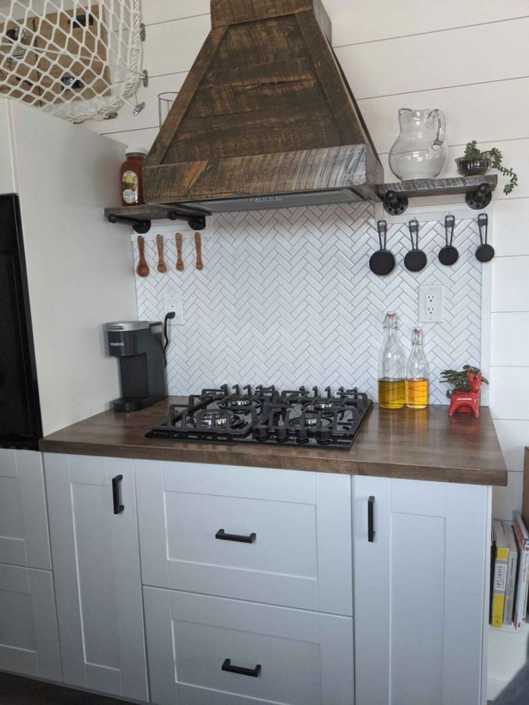 Gas burners on counter with stainless steel vent hood