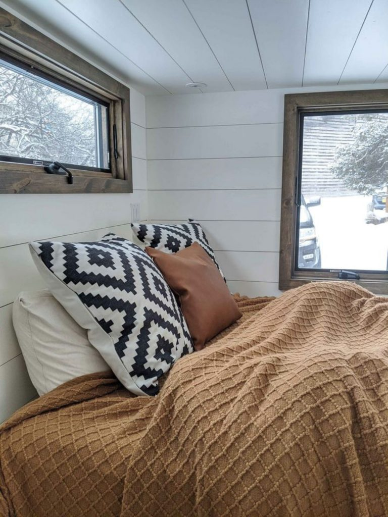 Tiny house bed with orange blanket