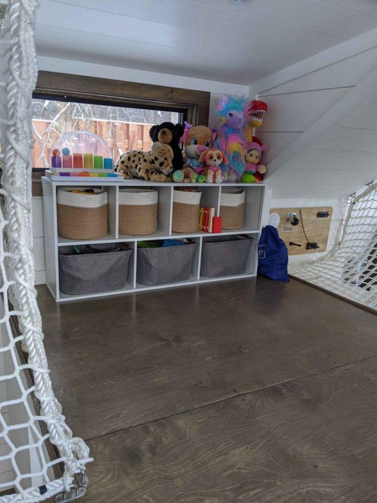 Toy bins in shelf on landing of tiny loft