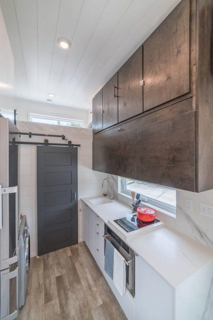 Dark stained cabinets above kitchen sink