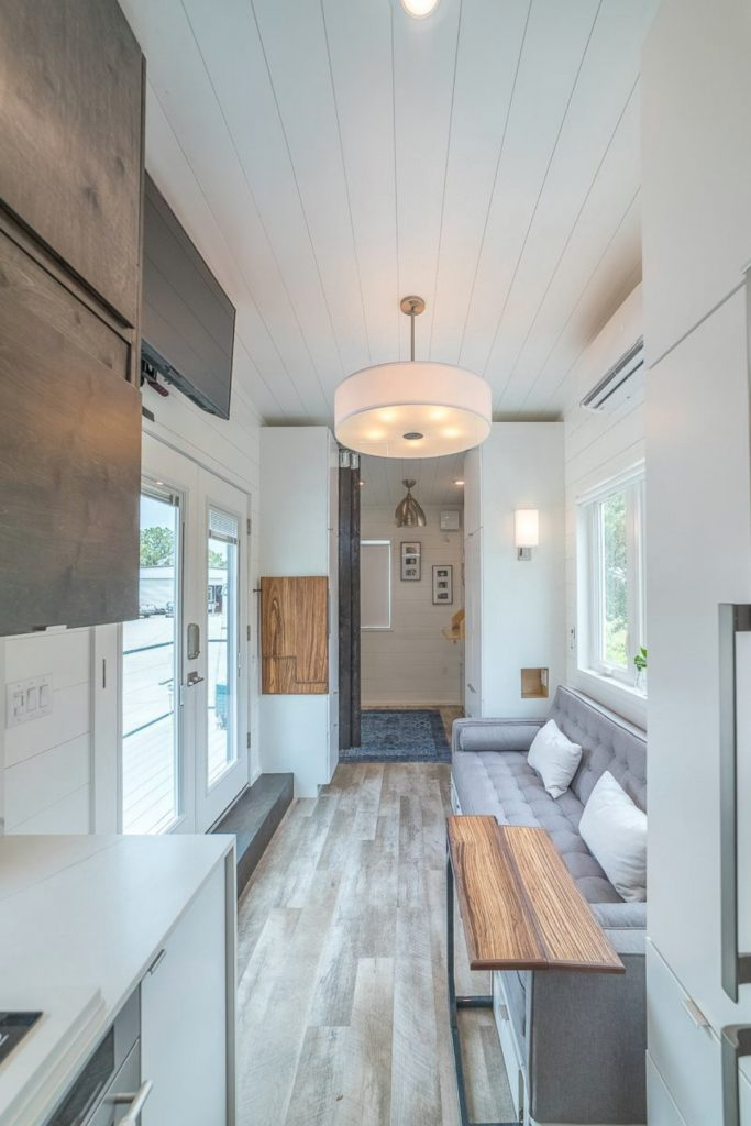 View of tiny house living room with charcoal sofa large dangling light and barn doors at end