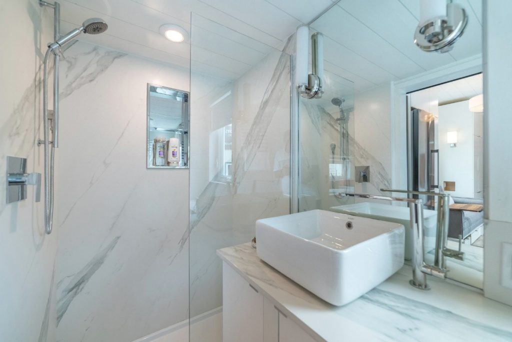All white tiled bathroom with large white bowl sink