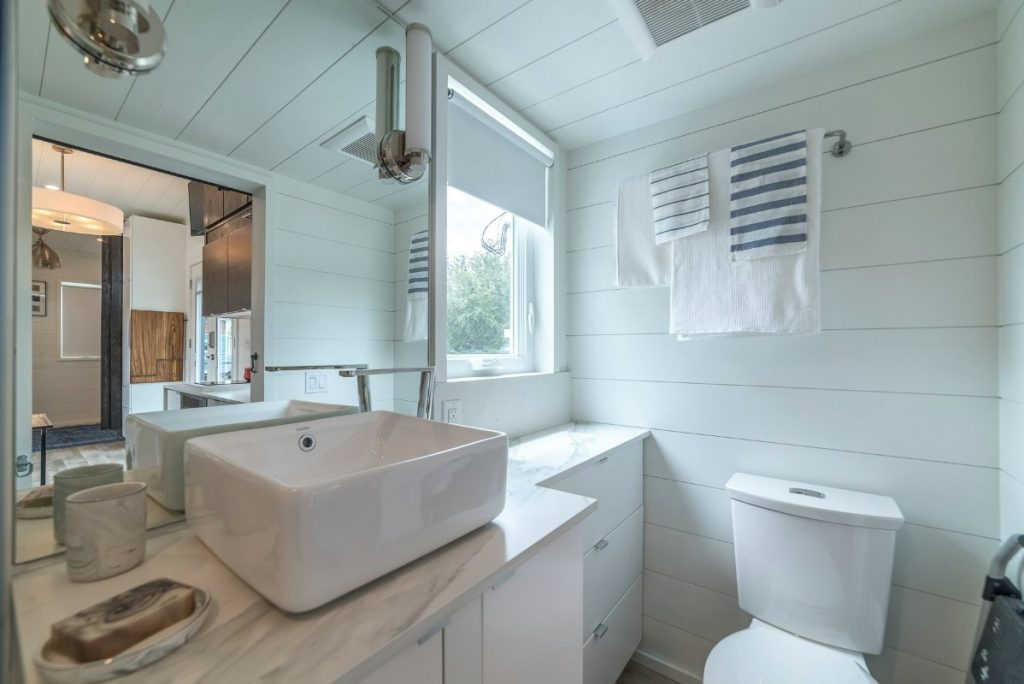 Bathroom vanity and view of toilet in tiny house
