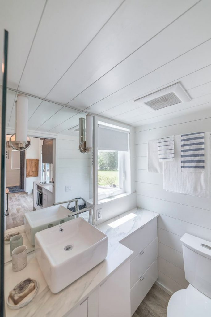 All white tiny house bathroom with mirror and windwo