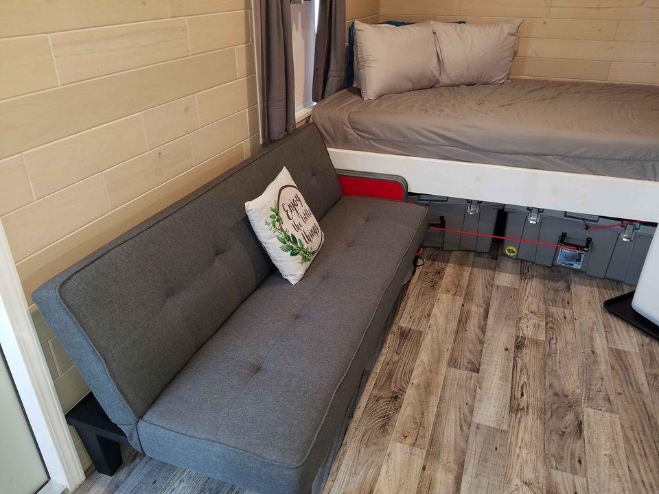 Grey futon sofa next to bed