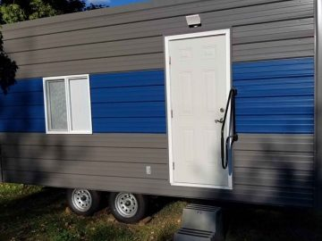 Grey and blue striped tiny house with white door
