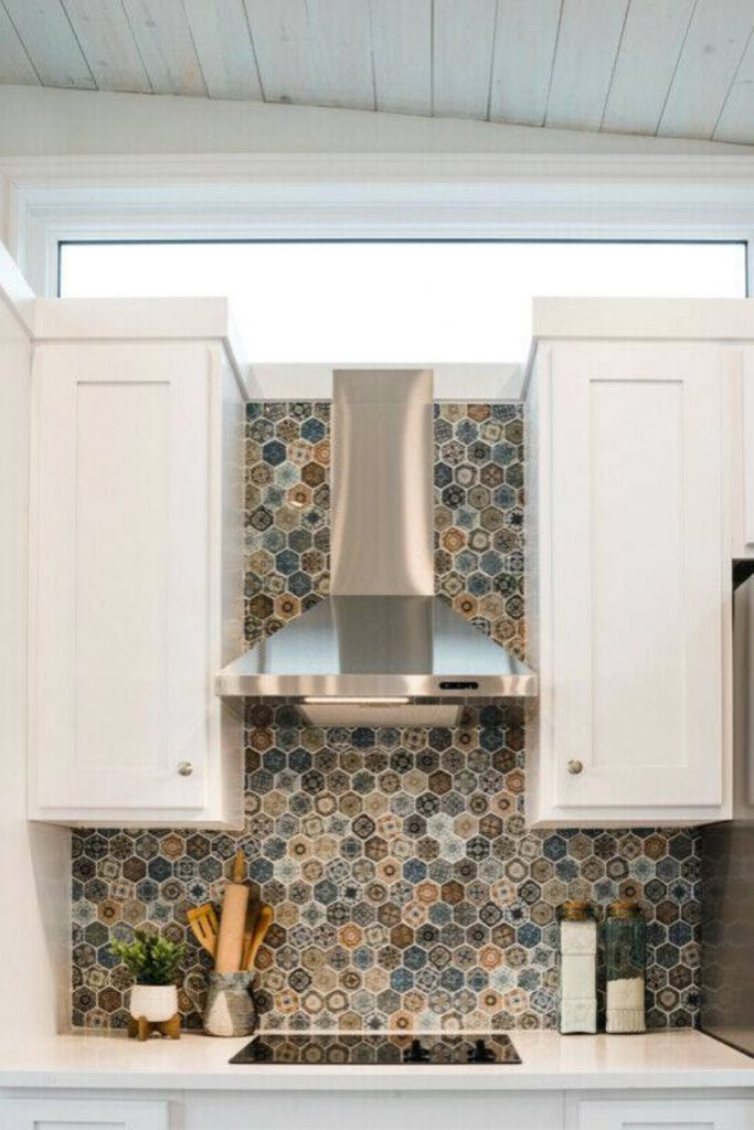Stainless steel vent hood with colorful tile between cabinets