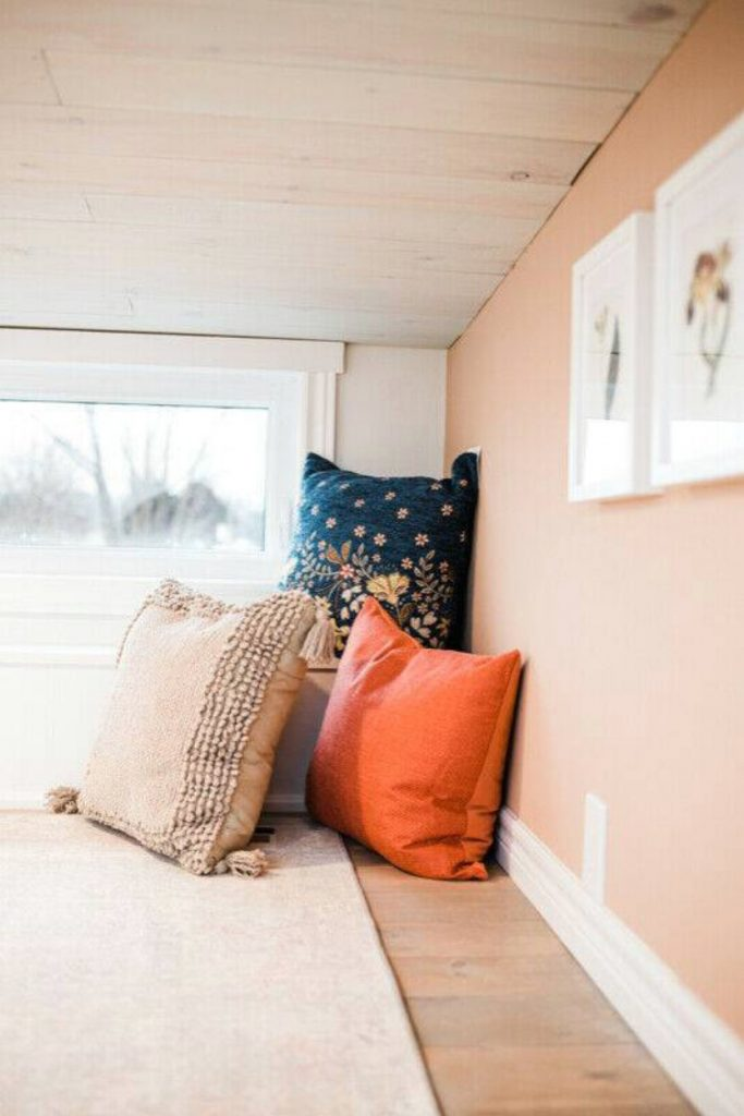 Three pillows propped on bed next to window