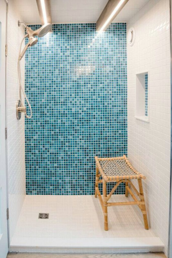 Large shower with teal tile wall and wood bench
