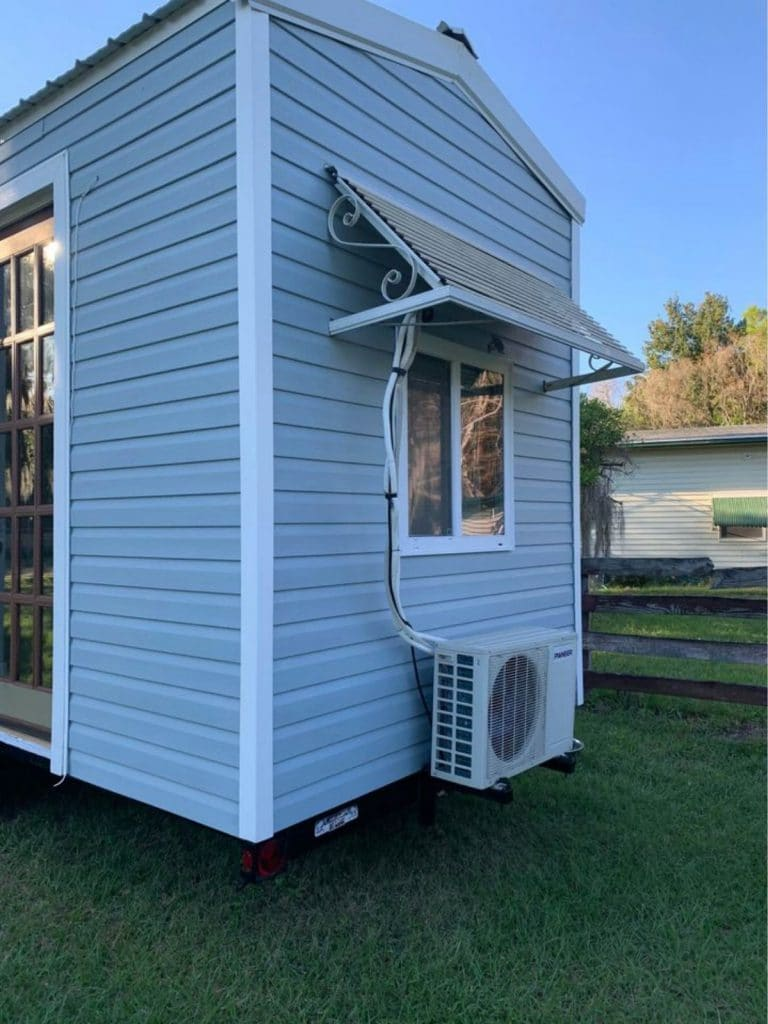 Back of tiny house showing window and air conditioner