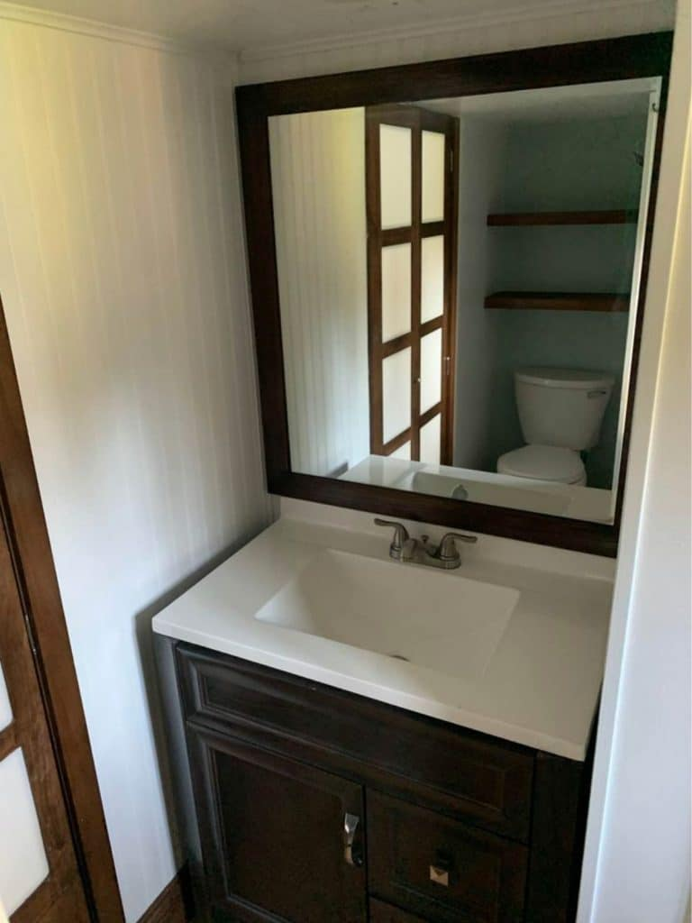 Dark wood vanity with white counter and large mirror