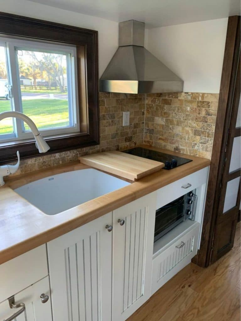 Large white kitchen sink with butcher block counter