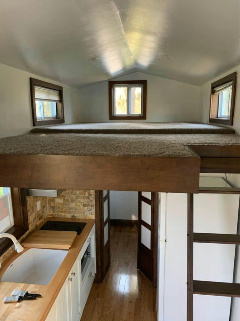 Carpeted loft with wooden ladder