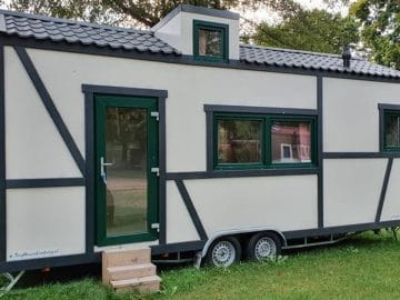 Black and white Bavarian look tiny house on wheels in yard