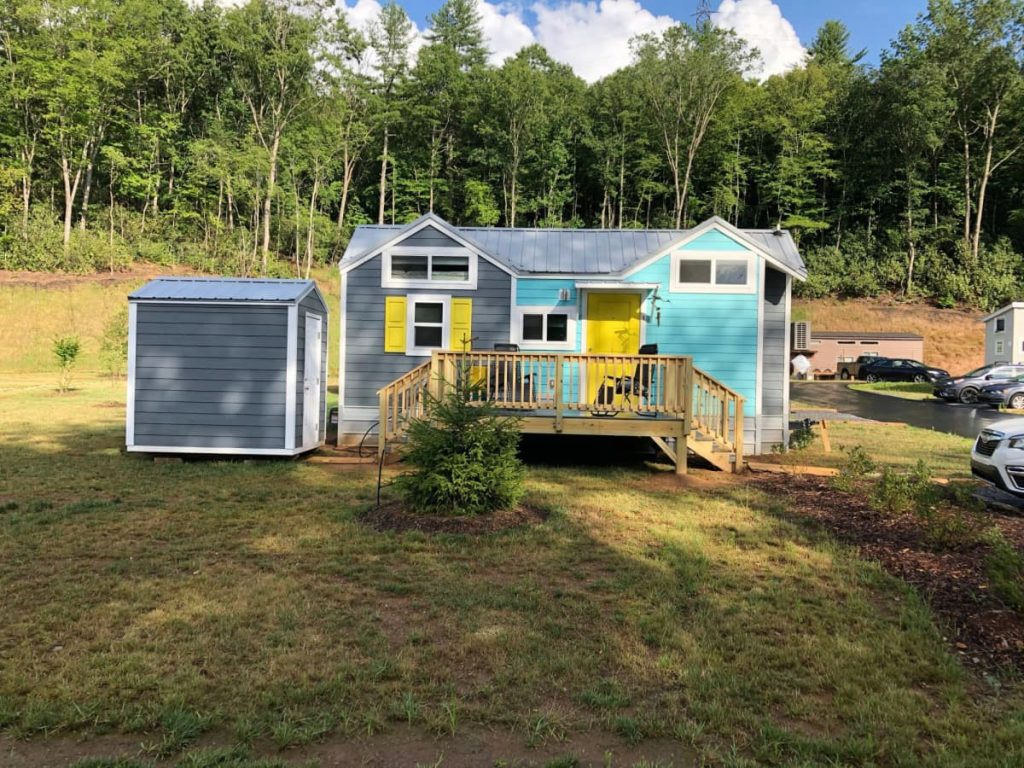 Tiny house on lot with grey shed and large porch