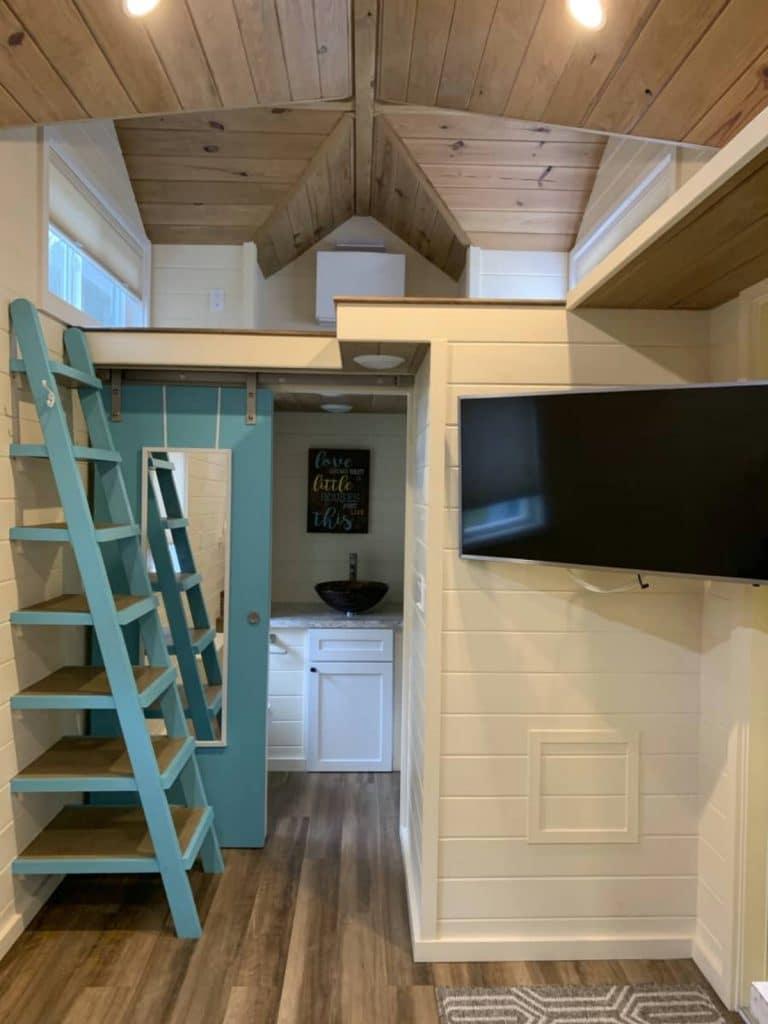 TV mounted in corner by door under loft