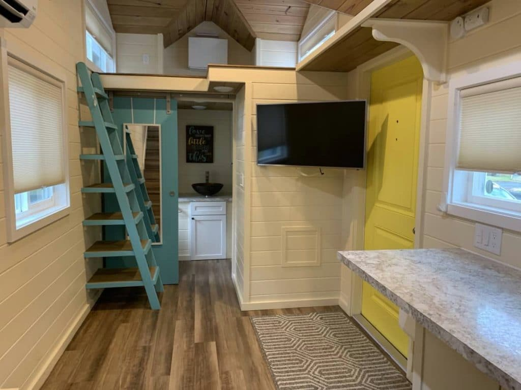 Tiny living space with teal ladder to loft and yellow door