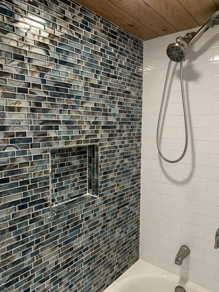 Colorful blue tile shower wall with built in shelf