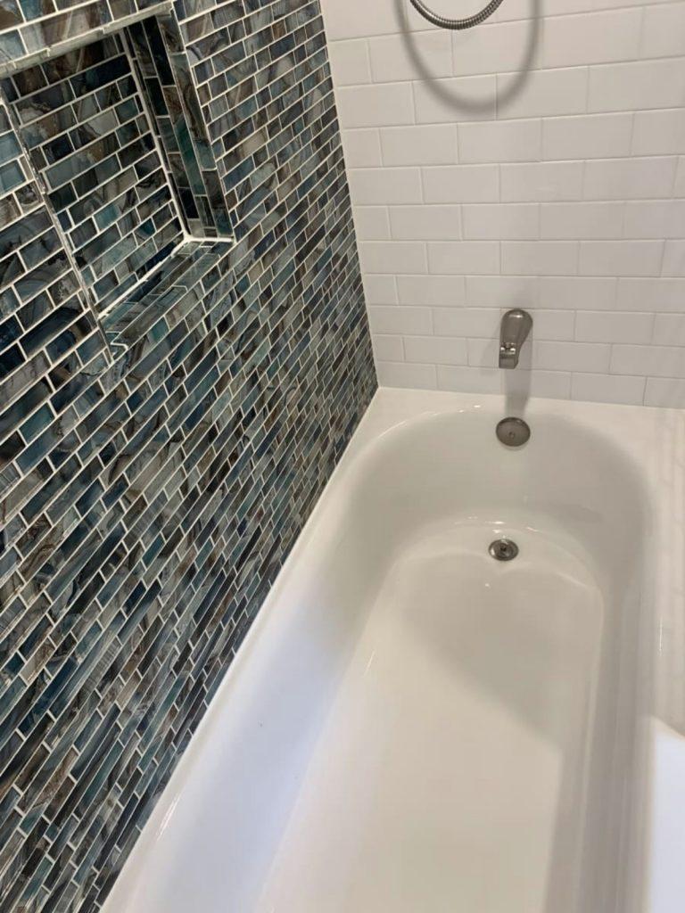 White bathtub with blue tile details on side