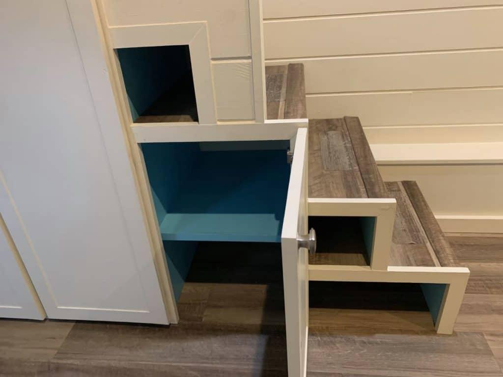 Open door on cabinet under stairs