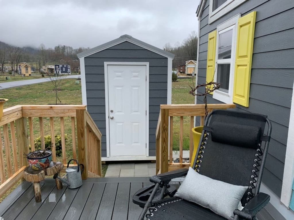View of small grey shed from porch