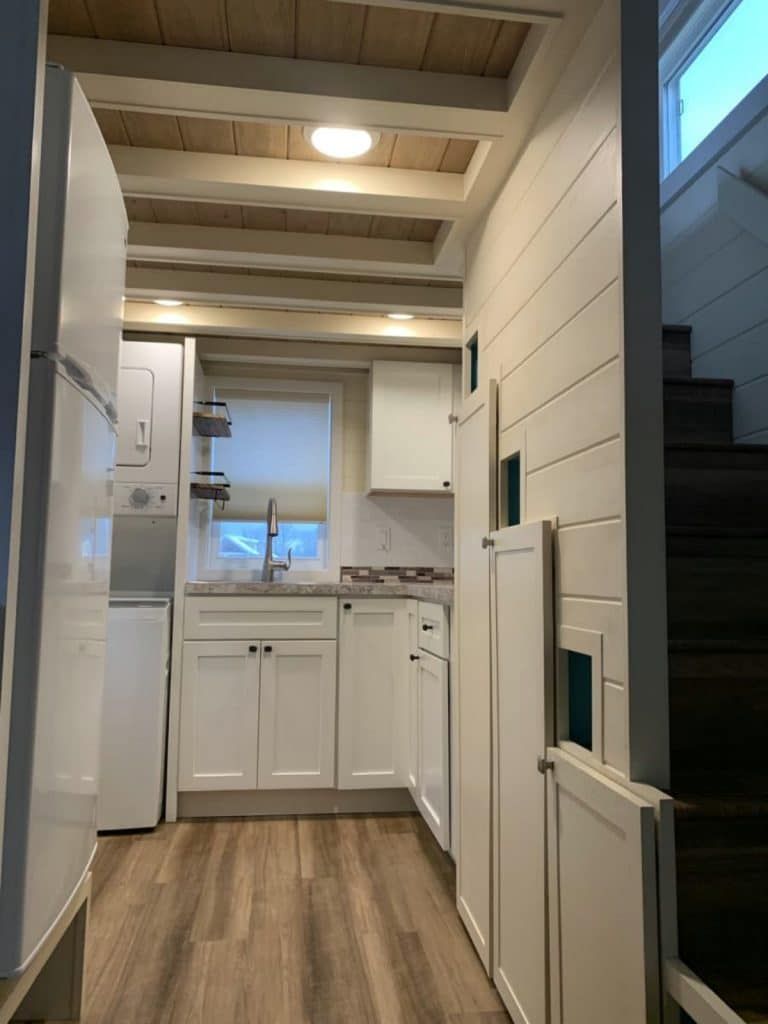 View from hall into kitchen with white and gray colors