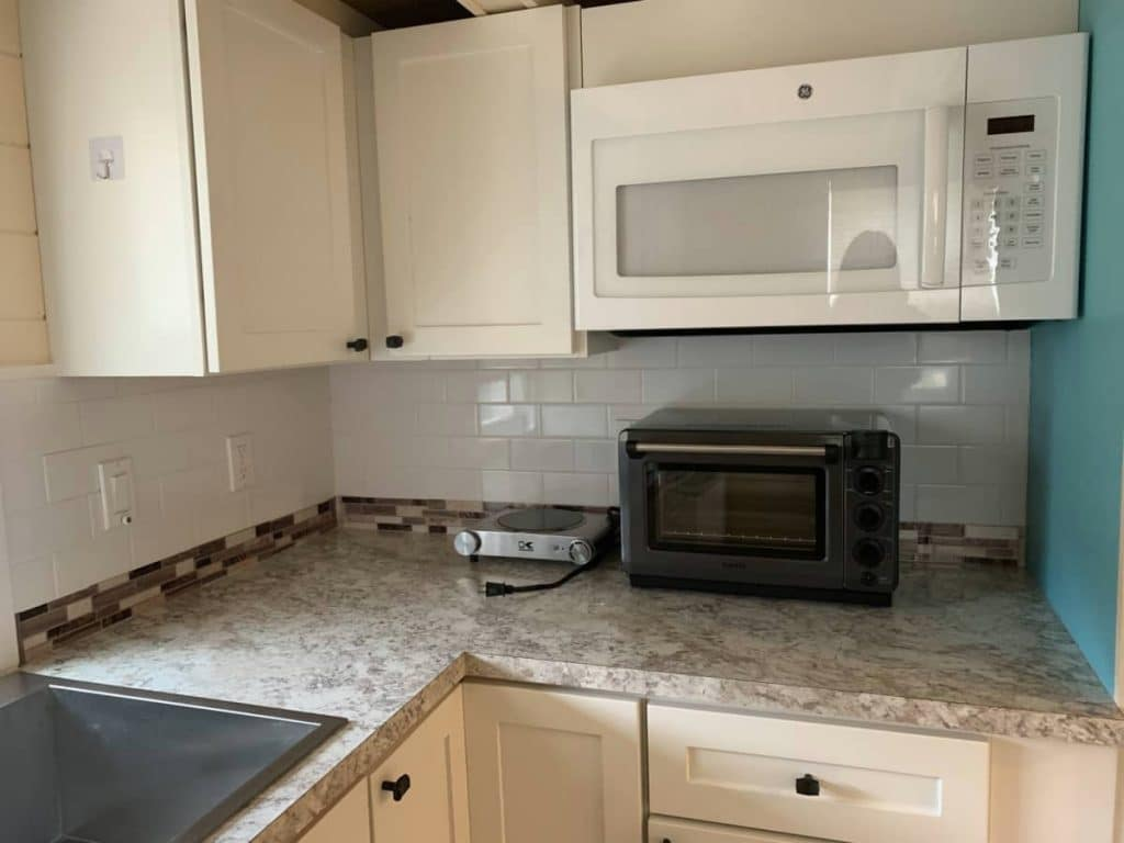White kitchen cabinets and counter with toaster oven and white microwave