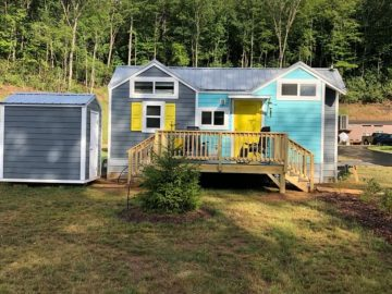 Tiny house with grey and teal siding with porch