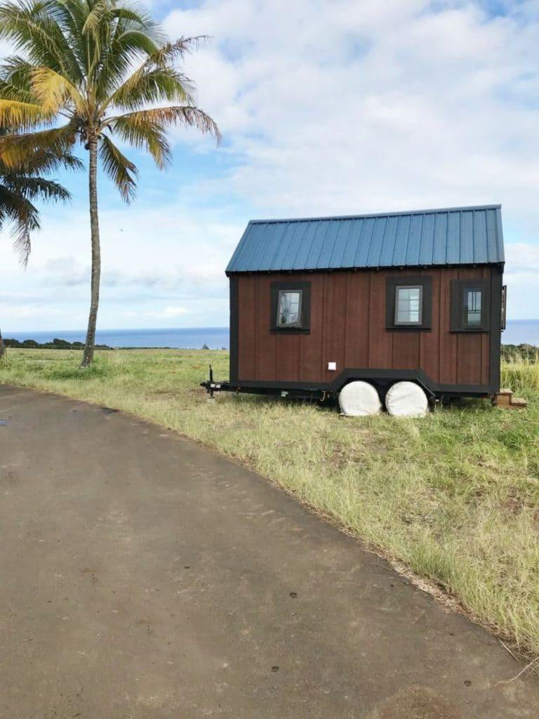 TIny house on wheels on grass by beach