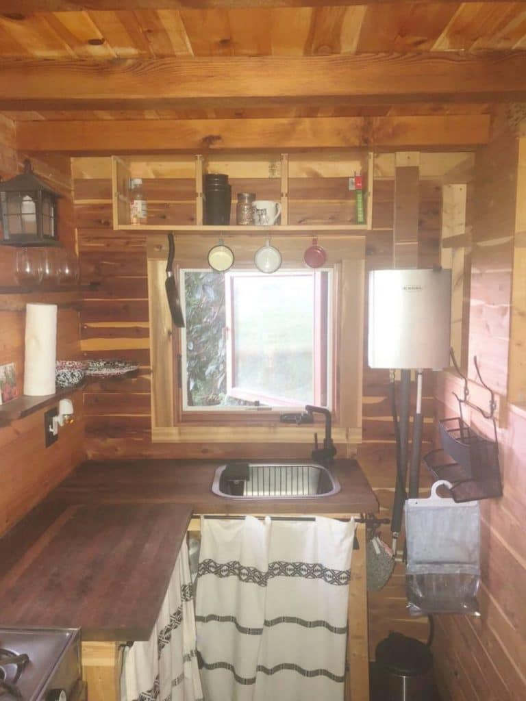 Kitchen in cedar cabin with curtains covering cabinets