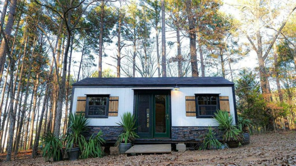 Tiny house with white siding and charcoal trim and roof