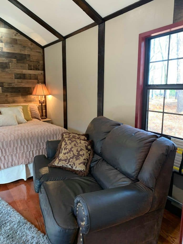 Large loveseat in front of bed with pink bedding