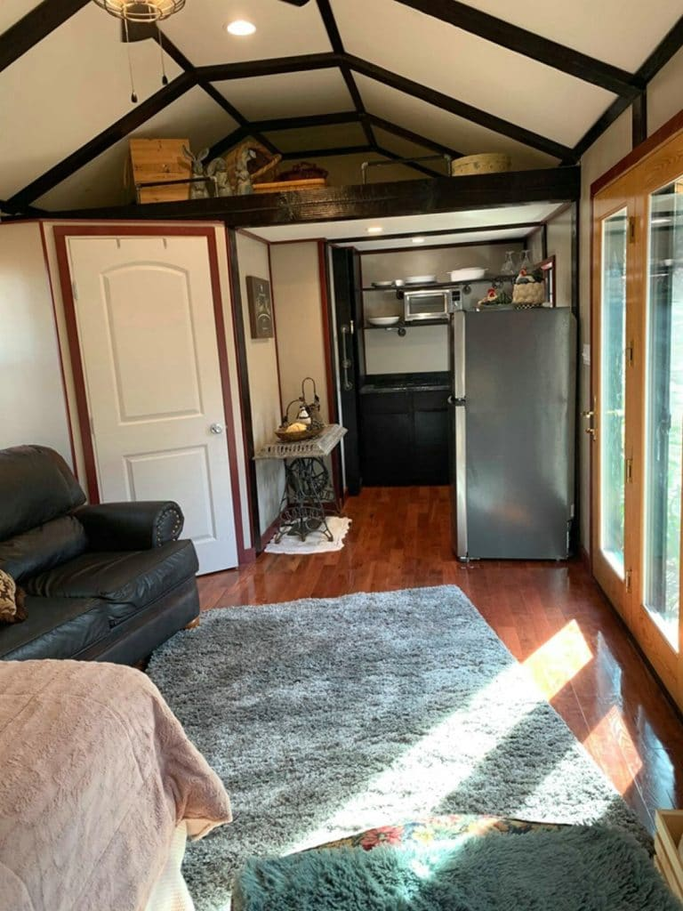 View into tiny house kitchen with loft above