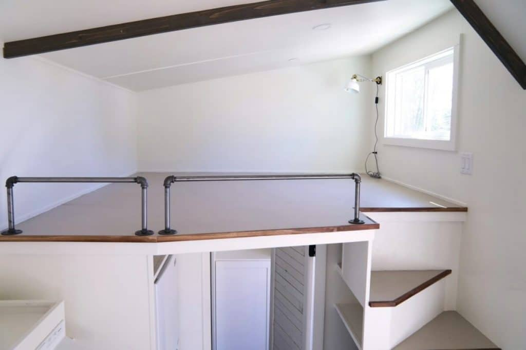 Open loft space with angled roofline and metal railing