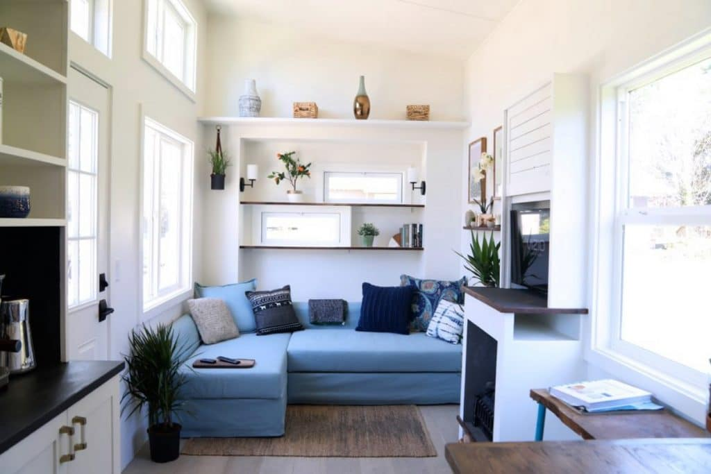 Blue sectional against white wall with shelves above