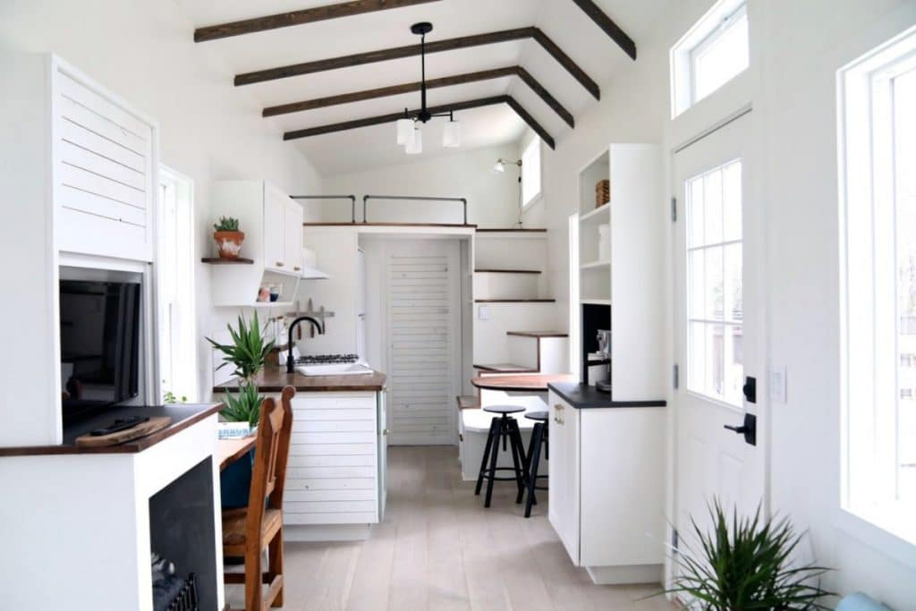 View into main kitchen space with white walls and wood open beams