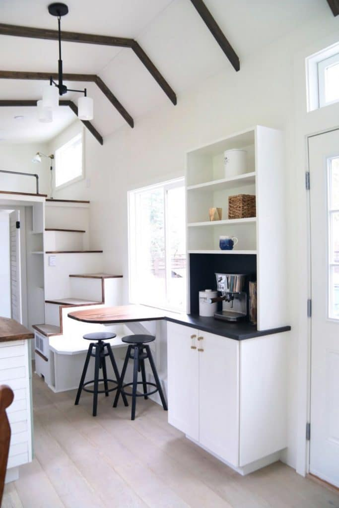 Hutch coffee station with white cabinets and shelves by dining table