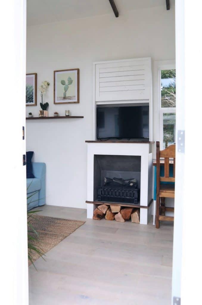 Fireplace in wall below TV next to window