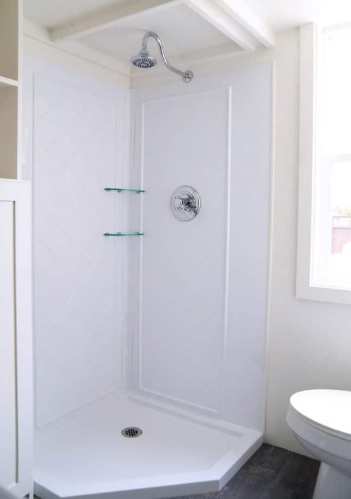 White corner shower stall in tiny bathroom