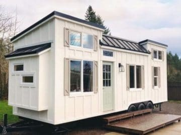 White tiny house with black roof