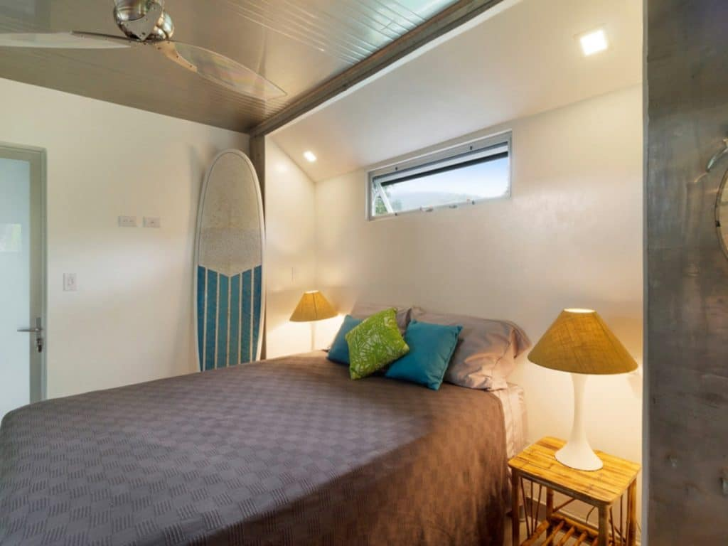 Bed next to white wall with small window and surf board in background