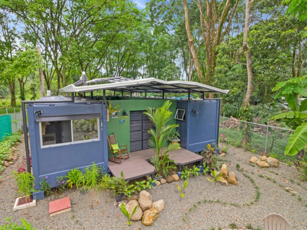 Shipping container home with blue exterior and green paint