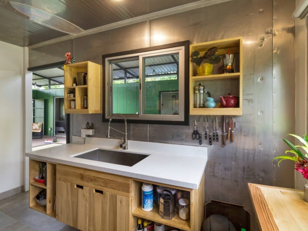 Blonde wood kitchen cabinets with open shelf and white countertop