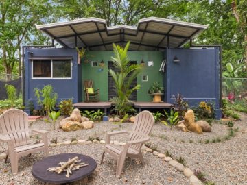 Blue shipping container home on rock yard