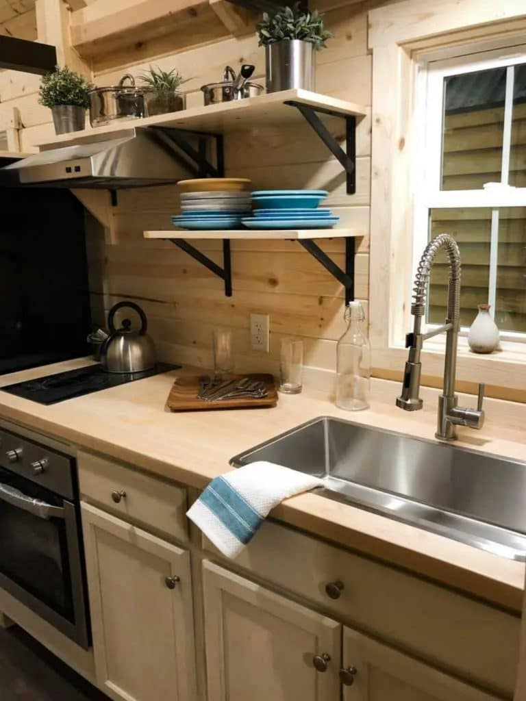 Stainless steel kitchen sink in light wood cabinets