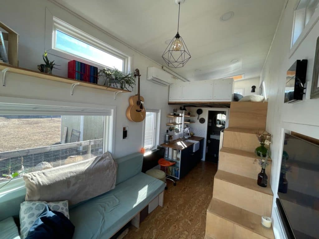 Tiny home main living space with windows on wall behind sofa